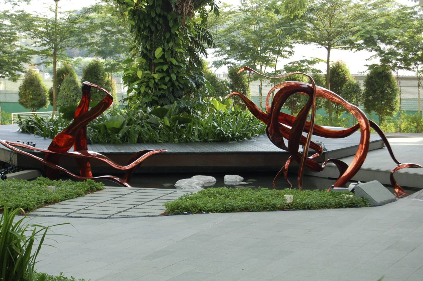 """I chose to make a sculpture of the SARS protease because Biopolis Scientists were so excited about their contributions to developing drug candidates for SARS in 2002-2003, a deadly Coronavirus. I chose to create the sculpture in a brilliant red patina over the bronze which adds a flash of color and movement to the plaza."""